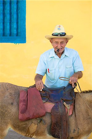 Portrait of old man wearing straw hat and smoking cigar, posing against a yellow wall with his donkey for tourist pesos, Trinidad, Cuba, West Indies, Central America Stock Photo - Rights-Managed, Code: 841-07081838