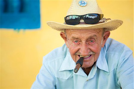 Portrait of old man wearing straw hat and smoking cigar, posing against a yellow wall for tourist pesos, Trinidad, Cuba, West Indies, Central America Stock Photo - Rights-Managed, Code: 841-07081839