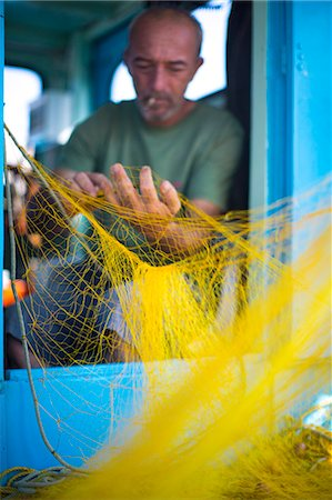 Fisherman cleaning his nets, Mykonos, Greek Islands, Greece, Europe Stock Photo - Rights-Managed, Code: 841-07202258