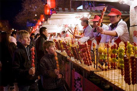 Boys eat candied strawberry sticks from stall in the Night Market, Wangfujing Street, Beijing, China Stock Photo - Rights-Managed, Code: 841-07457239