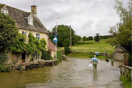 Man wades through flood water in Swinbrook, Oxfordshire, England, United Kingdom Stock Photo - Rights-Managed, Code: 841-07523521
