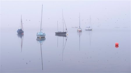 fog (weather) - Swallows flying past boats on a foggy autumn morning at Wimbleball Lake, Exmoor, Somerset, England, United Kingdom, Europe Stock Photo - Rights-Managed, Code: 841-07590324