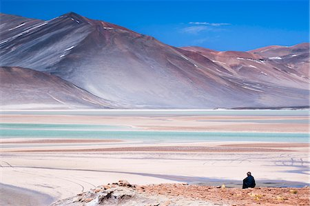 extreme terrain - Man sitting on rocks at Miscanti Volcano and high plateau lagoon in San Pedro de Atacama desert, Chile, South America Stock Photo - Rights-Managed, Code: 841-07673548