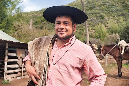 Portrait of a Chilean cowboy (arriero) in a hat on a horse farm in El Toyo region of Cajon del Maipo, Chile, South America Stock Photo - Rights-Managed, Code: 841-07673552