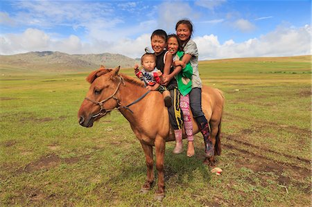Four nomad siblings on their tame horse at summer nomad camp, Khujirt, Uvurkhangai, Central Mongolia, Central Asia, Asia Stock Photo - Rights-Managed, Code: 841-08239963