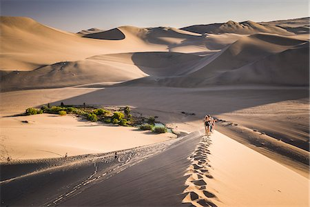 Tourists climbing sand dunes at sunset at Huacachina, a village in the desert, Ica Region, Peru, South America Stock Photo - Rights-Managed, Code: 841-08421097