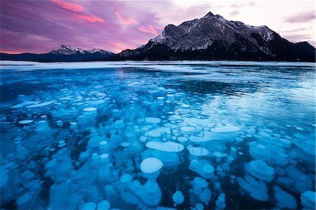 Bubbles and Cracks in the Ice with Mount Michener and Kista Peak in the Background at Sunrise, Abraham Lake, Alberta, Canada, North America Stock Photo - Rights-Managed, Code: 841-08527719