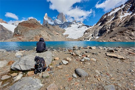 people in argentina - A lone figure in mountain gear rests on rocks with view to Lago de los Tres and Mount Fitz Roy, their backpack on the ground, Patagonia, Argentina, South America Stock Photo - Rights-Managed, Code: 841-08887432