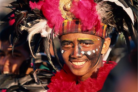 pictures philippine festivals philippines - Portrait of a man with facial decoration and head-dress with feathers at Mardi Gras carnival, Dinagyang in Iloilo City on Panay Island, Philippines, Southeast Asia, Asia Stock Photo - Rights-Managed, Code: 841-02899066
