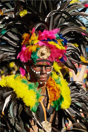 pictures philippine festivals philippines - Portrait of a man with facial decoration and head-dress with feathers at Mardi Gras carnival, Dinagyang in Iloilo City on Panay Island, Philippines, Southeast Asia, Asia Stock Photo - Rights-Managed, Code: 841-02899067