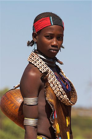 Hamer lady wearing traditional goat skin dress decorated with cowie shells, carrying kalash on her way to market, Dombo village, Turmi, Lower Omo valley, Ethiopia, Africa Stock Photo - Rights-Managed, Code: 841-02916992