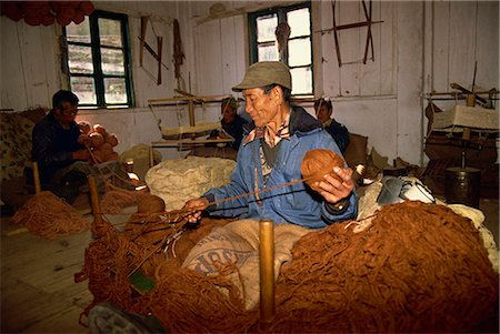 Portrait of a Tibetan man spinning wool in a carpet factory at a self-help centre in Darjeeling, India, Asia Stock Photo - Rights-Managed, Code: 841-02946990