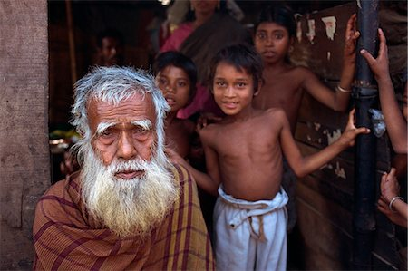 dhaka - Head and shoulders portrait of an old Bangladeshi (Bengali) man with a white beard, and children beyond, looking at the camera, in the slums of Dhaka (Dacca), Bangladesh, Asia Stock Photo - Rights-Managed, Code: 841-02947178