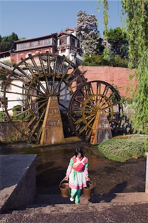 A Bai girl carrying buckets of water in front of a water wheel in Lijiang Old Town, UNESCO World Heritage Site, Yunnan Province, China, Asia Stock Photo - Rights-Managed, Code: 841-03056041