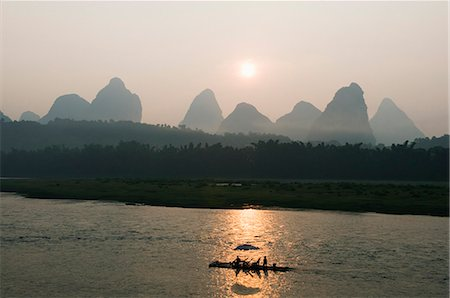 Tourist boat sailing through karst scenery at sunrise on the Li river (Lijiang) in Yangshuo, near Guilin, Guangxi Province, China, Asia Stock Photo - Rights-Managed, Code: 841-03056083