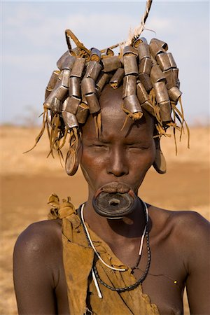 Portait of a Mursi girl with clay lip plate, and hairstyle that indicates she is going through puberty,The Mursi Hills, Mago National Park, Lower Omo Valley, Ethiopia, Africa Stock Photo - Rights-Managed, Code: 841-03505106