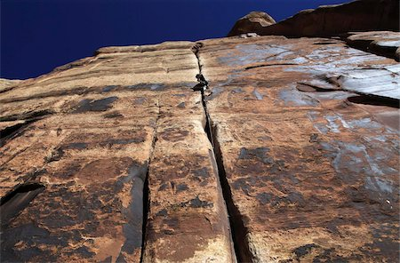 A rock climber tackles an overhanging crack in a sandstone wall on the cliffs of Indian Creek, a famous rock climbing area in Canyonlands National Park, near Moab, Utah, United States of America, North America Stock Photo - Rights-Managed, Code: 841-03675354