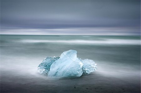 Piece of glacial ice washed ashore by the incoming tide near glacial lagoon at Jokulsarlon, Iceland, Polar Regions Stock Photo - Rights-Managed, Code: 841-03672449