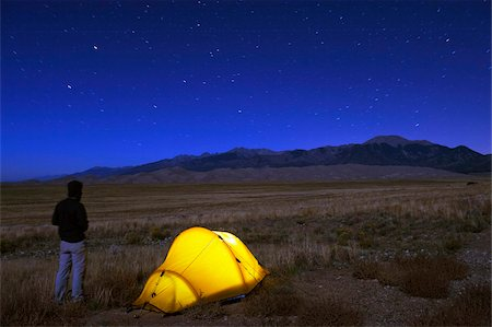 Hiker and tent illuminated under the night sky, Great Sand Dunes National Park, Colorado, United States of America, North America Stock Photo - Rights-Managed, Code: 841-03868516