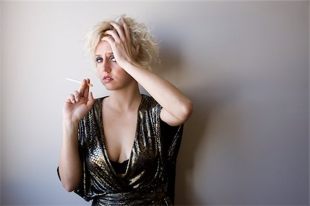 Worried young blonde woman in sexy cocktail dress smoking cigarette Stock Photo - Rights-Managed, Code: 842-05979349
