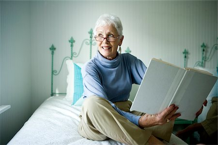 Portrait of senior woman sitting on bed with book smiling Stock Photo - Rights-Managed, Code: 842-05979549