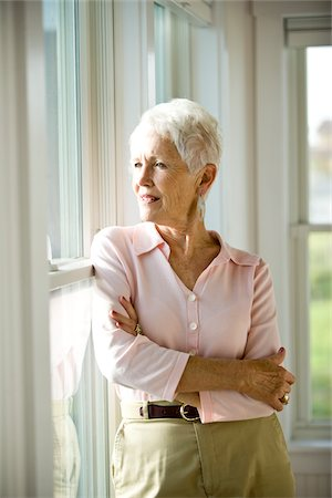 Senior woman leaning against windows gazing out Stock Photo - Rights-Managed, Code: 842-05979541