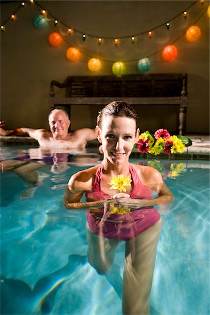 seniors woman in swimsuit - Middle-aged woman holding flower in swimming pool, man in background Stock Photo - Rights-Managed, Code: 842-05979609