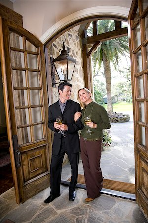 Interracial couple drinking wine walking through front door of elegant home Stock Photo - Rights-Managed, Code: 842-05979745