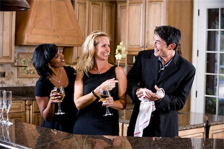 Three multi-racial adult friends laughing together in kitchen drinking wine Stock Photo - Rights-Managed, Code: 842-05979754