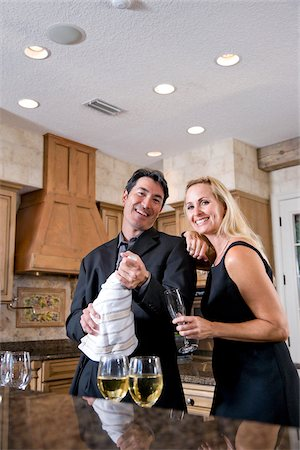 Mid-adult interracial couple opening bottle of champagne in kitchen of home Stock Photo - Rights-Managed, Code: 842-05979750