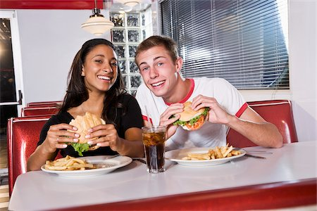 Interracial teen couple eating burgers in restaurant Stock Photo - Rights-Managed, Code: 842-05979835