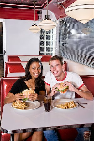 Interracial teen couple eating burgers in diner Stock Photo - Rights-Managed, Code: 842-05979836