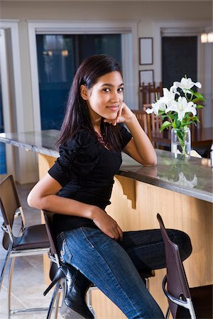 Pretty Hispanic teenage girl at home sitting at kitchen counter Stock Photo - Rights-Managed, Code: 842-05979916