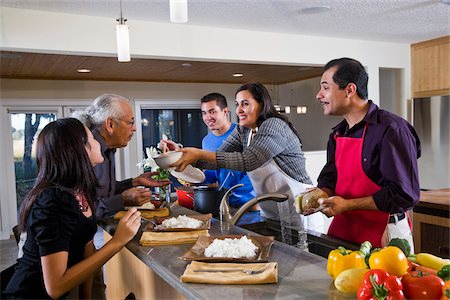 Hispanic mother serving home-cooked meal to family in kitchen Stock Photo - Rights-Managed, Code: 842-05979917