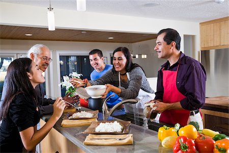 Hispanic mother serving home-cooked meal to family in kitchen Stock Photo - Rights-Managed, Code: 842-05979919
