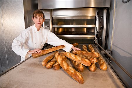 professional (pertains to traditional blue collar careers) - Mature woman taking baked loaves of bread out of commercial baker oven Stock Photo - Rights-Managed, Code: 842-05980044