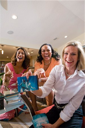Portrait of three happy multi-ethnic women showing photographs in living room Stock Photo - Rights-Managed, Code: 842-02649613