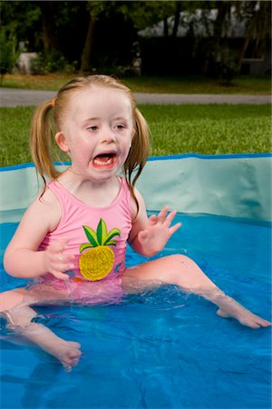 Side view of a girl with downs syndrome playing in kiddie pool Stock Photo - Rights-Managed, Code: 842-02654144