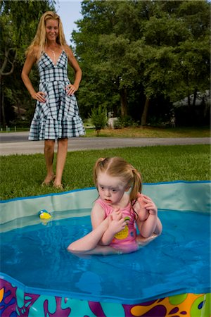 Girl with downs syndrome playing in kiddie pool with mother watching in background Stock Photo - Rights-Managed, Code: 842-02654147