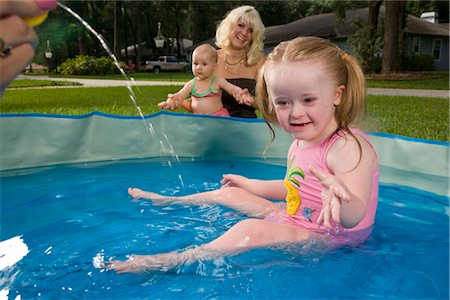 Girl with downs syndrome playing in kiddie pool with mother and baby watching in background Stock Photo - Rights-Managed, Code: 842-02654152