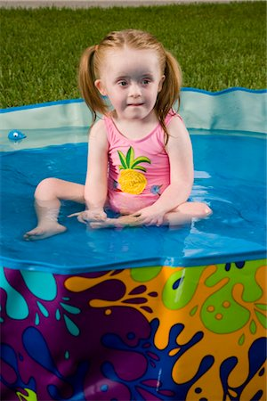 View of a girl with downs syndrome playing in kiddie pool Stock Photo - Rights-Managed, Code: 842-02654160
