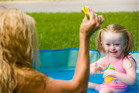 Portrait of mother playing with daughter with downs syndrome, in kiddie pool Stock Photo - Rights-Managed, Code: 842-02654188