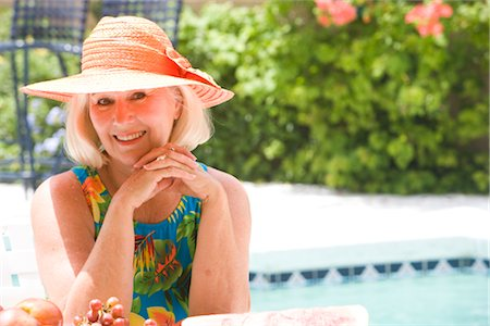 seniors woman in swimsuit - Portrait of mature woman sitting beside table with fruit by swimming pool Stock Photo - Rights-Managed, Code: 842-02654993