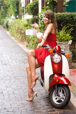 Portrait of young woman sitting on motor scooter outside a shop Stock Photo - Rights-Managed, Code: 842-02655394