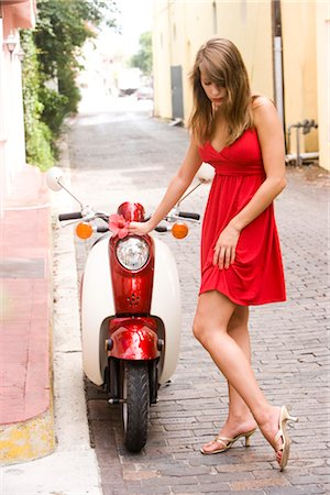 sexy women legs - Attractive young woman standing by motor scooter holding flower Stock Photo - Rights-Managed, Code: 842-02655400