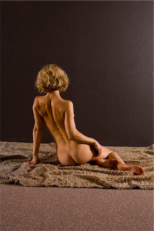 Rear view of young nude woman sitting on blanket, studio shot Stock Photo - Rights-Managed, Code: 842-02650234