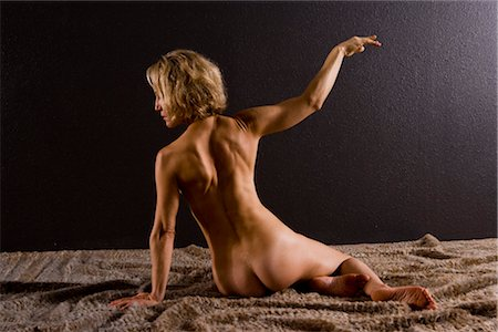 Rear view of young nude woman sitting on blanket holding a pose, studio shot Stock Photo - Rights-Managed, Code: 842-02650235