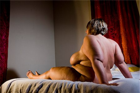Overweight nude woman sitting on bed in bedroom, side view Stock Photo - Rights-Managed, Code: 842-02650275