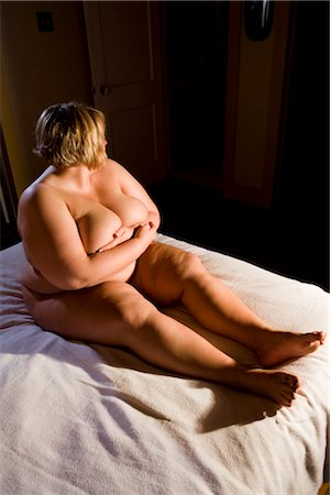 Overweight nude woman sitting on bed in bedroom, side view Stock Photo - Rights-Managed, Code: 842-02650276