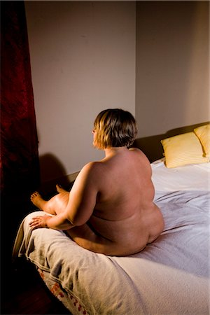 Overweight nude woman sitting on bed in bedroom, rear view Stock Photo - Rights-Managed, Code: 842-02650272